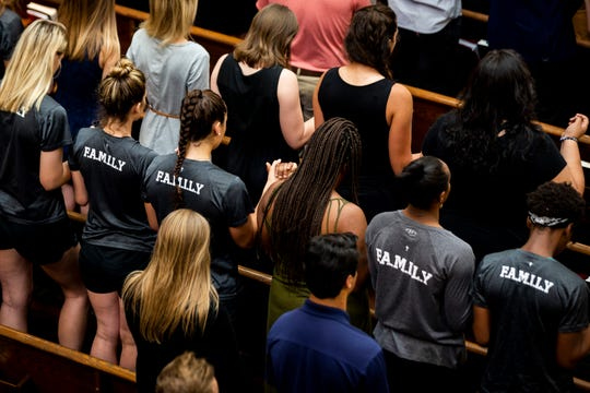 Mass attendees hold hands as they pray the Our Father during a memorial Mass for Emily Acosta at Ave Maria Parish Church in Ave Maria, on Thursday, Feb. 21, 2019. Acosta, who was a junior at Ave Maria University, died in a car crash on Wednesday afternoon on Oil Well Road.