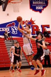 Lakewood sophomore Ryan Davis shoots against defense from Centerburg junior Hayden Sutton during Wednesday night's game. The Lancers won 49-46.