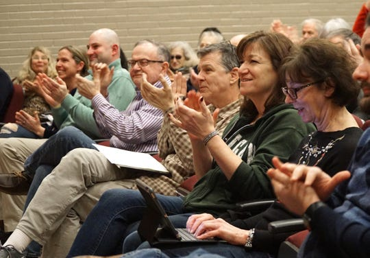 Attendees of Haley Stevens' Feb. 20 meeting at Milford High applaud one of the congresswoman's points.