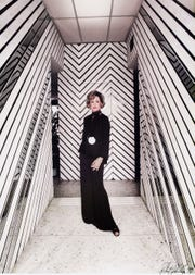Nelda Linsk in the entry hall to the second home Arthur Elrod designed for her and her husband, Joseph, on Camino Norte in Palm Springs. The walls are wrapped in bands of lacquered fabric, mirrored glass and wood slats.