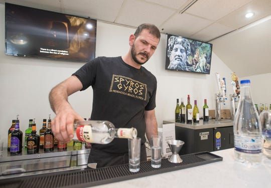 Owner Spyros Petrovits pours shots of ouzo Thursday at Spyros' Authentic Greek Restaurant & Bar on Cervantes Street in Pensacola.