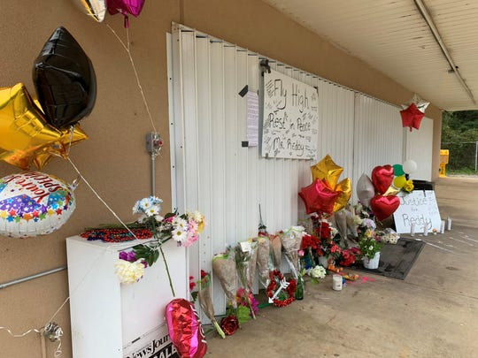 "Flowers, card and balloons line the front of the Quick Fill store where beloved store clerk Kotha Govardhan, known as ""Reddy,"" was shot and killed on Tuesday night."