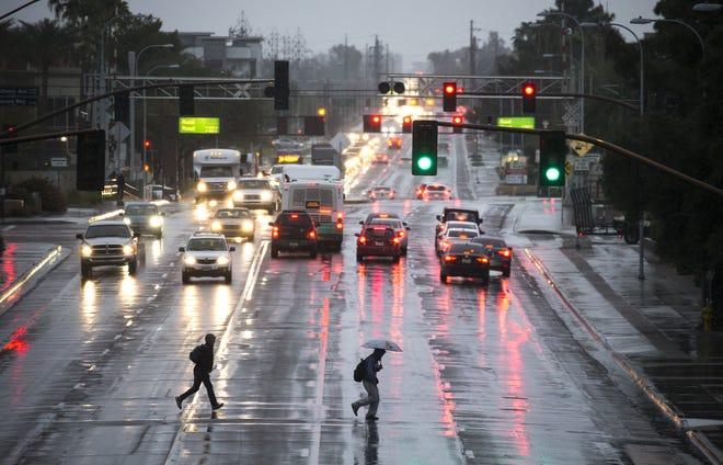 Pedestrians cross University Drive in the rain on Feb. 21, 2019, at ASU's Tempe campus.