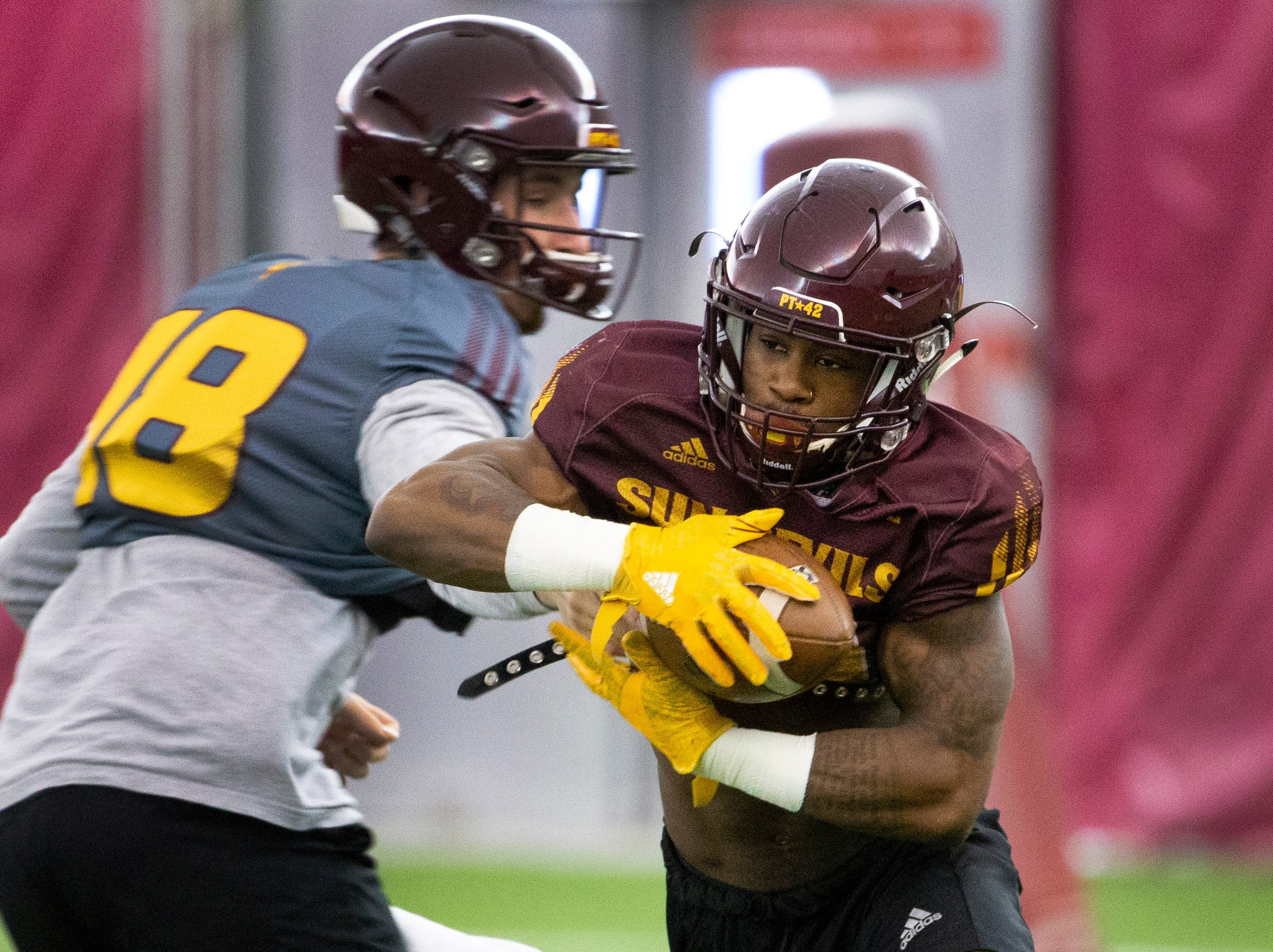 Quarterback Langston Frederick hands off the ball to running back Isaiah Floyd during a drill at ASU spring football practice in the Verde Dickey Dome in Tempe on February 21.