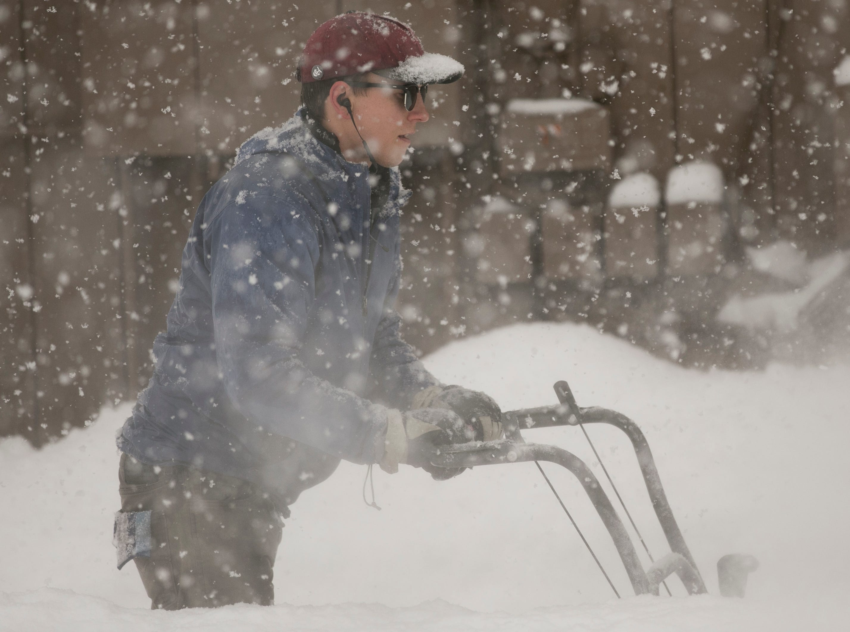 Dustin Brady cleans sidewalks in the snow near Northern Arizona University in Flagstaff on Feb. 21, 2019. A storm was expected to bring 20-30 inches of snow around northern Arizona through Friday.