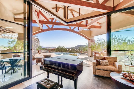 The 5,517-square-foot Scottsdale house, purchased by The Mark Daryl Geweke Trust and Wendy Geweke, features retractable floor-to-ceiling glass walls and a backyard with a negative-edge pool.