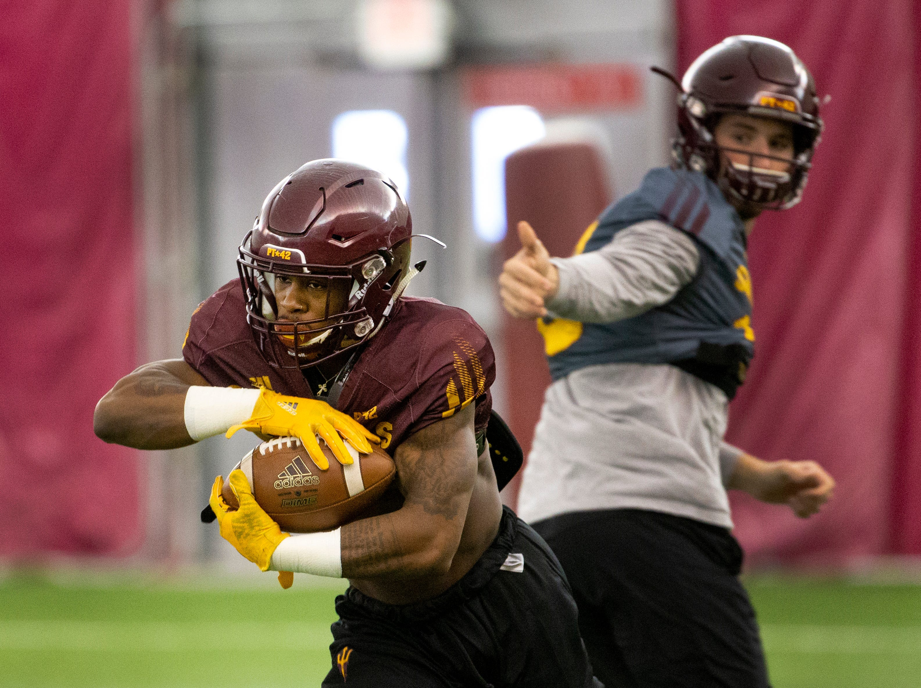 Running back Isaiah Floyd takes the ball from quarterback Langston Frederick during a drill at ASU spring football practice in the Verde Dickey Dome in Tempe on February 21.