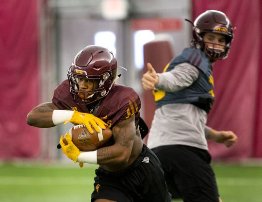 Running back Isaiah Floyd takes the ball from a quarterback during a drill at ASU spring football practice in the Verde Dickey Dome in Tempe on February 21.