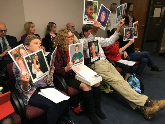 At a Senate Transportation and Public Safety committee meeting, people hold up photos of victims who died after being hit by distracted drivers.