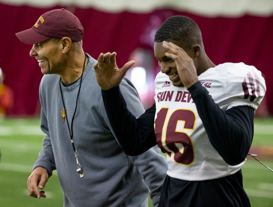 ASU head football coach Herm Edwards jokes with safety Aashari Crosswell during ASU spring football practice in the Verde Dickey Dome in Tempe on February 21.
