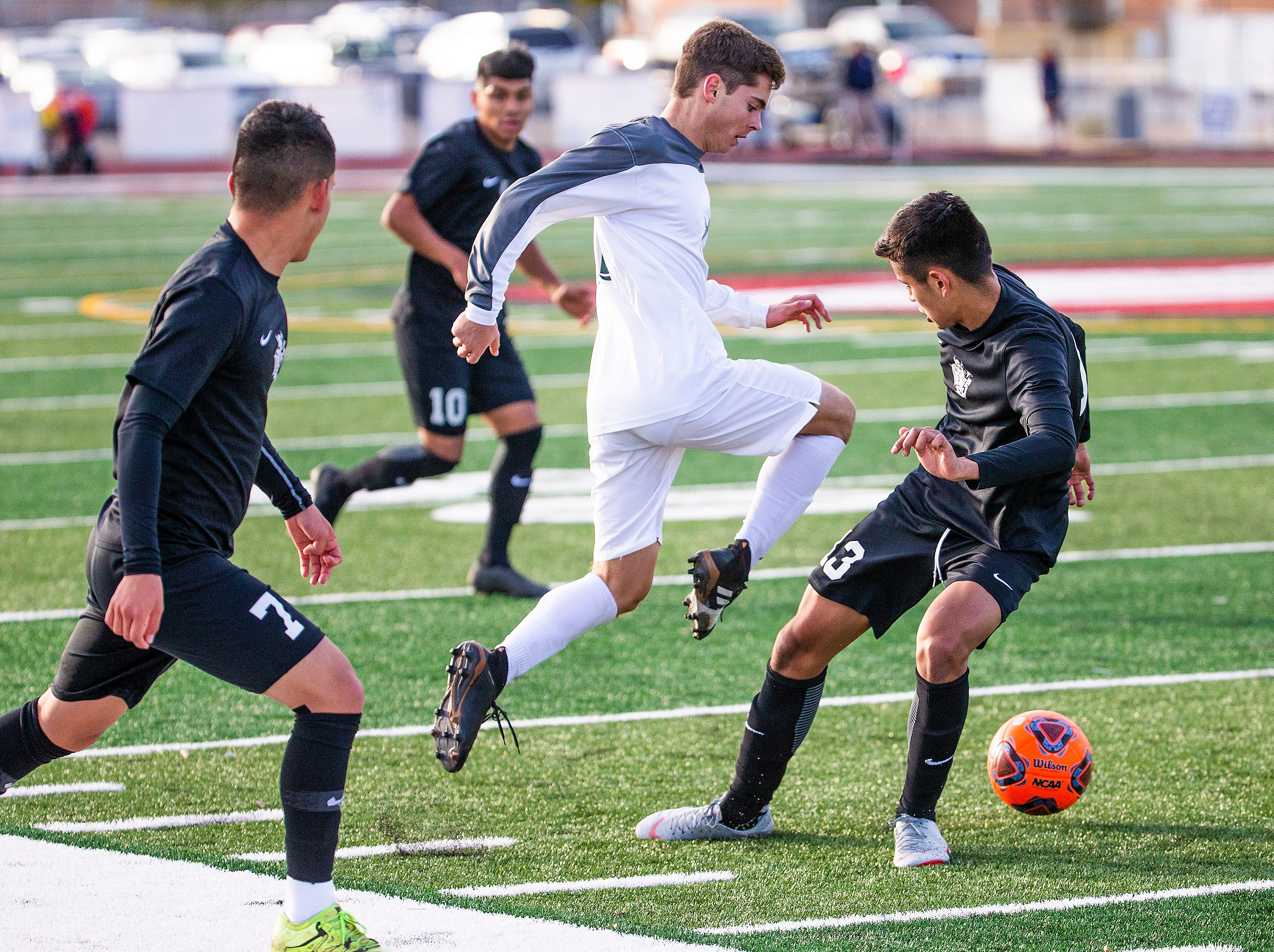 Tucson Sunnyside High School players Adrian Virgen, left, and Carlos Frias, right, converge on Campo Verde High School player Shawn McGarvin         during the 5A State Soccer Championship at Coronado High School in Scottsdale, Wednesday, February 20, 2019.