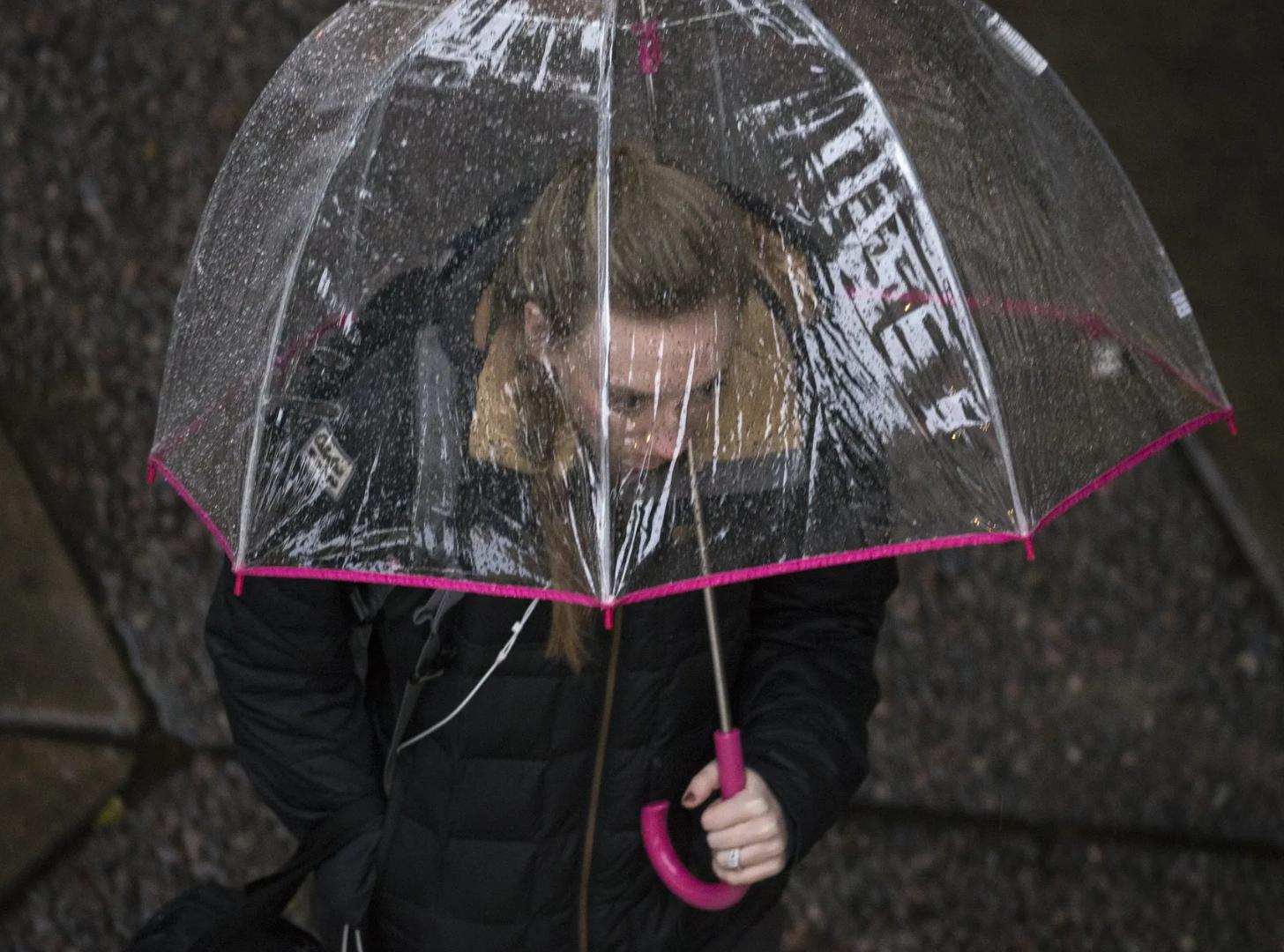 Gente se protege de la lluvia el 21 de febrero, 2019, en centro de Phoenix y Tempe, Arizona.