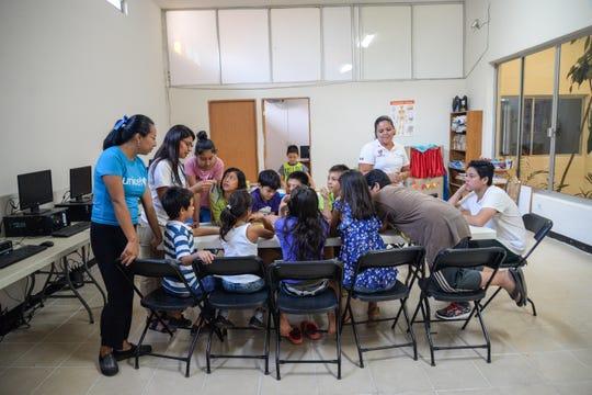 Personal del albergue Centro de Día interactúa con niños integrantes de la caravana de migrantes hondureños