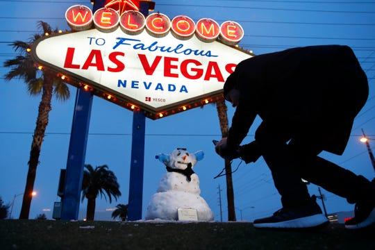 Un hombre toma una fotografía a un mono de nieve, colocado bajo el letrero luminoso de Las Vegas.