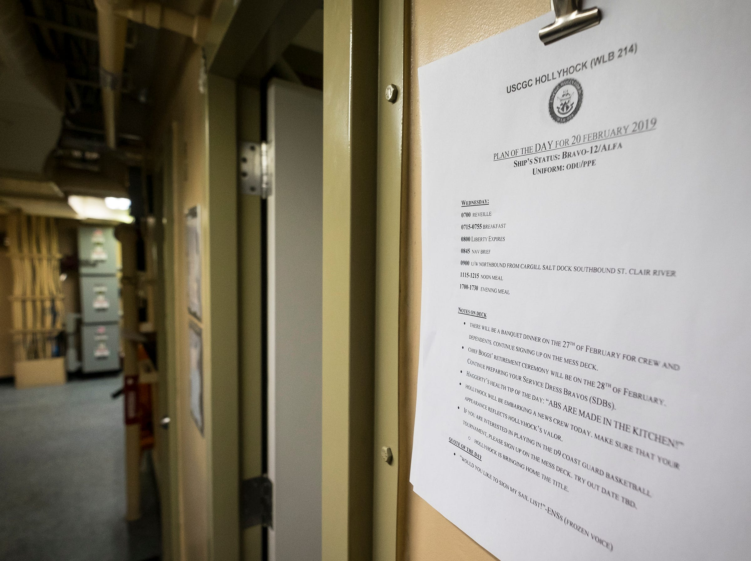 A plan outlining the day's objectives hangs outside one of the offices on one of the Hollyhock's lower decks.