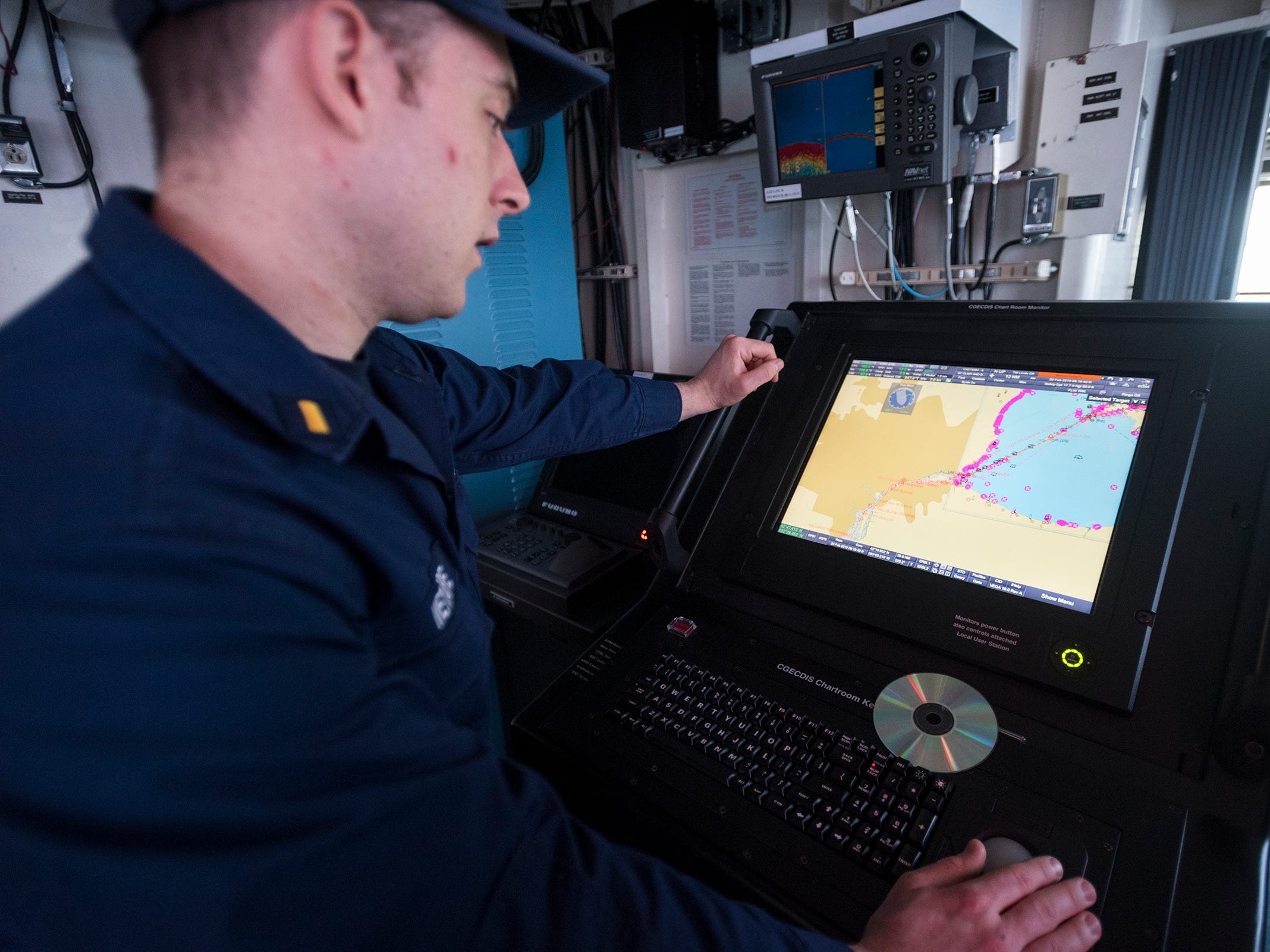 Ensign Kevin Wetmore talks about ECDIS, a computer system onboard the USCGC Hollyhock Wednesday, Feb. 20, 2019. ECDIS integrates different navigation systems and digital charts.