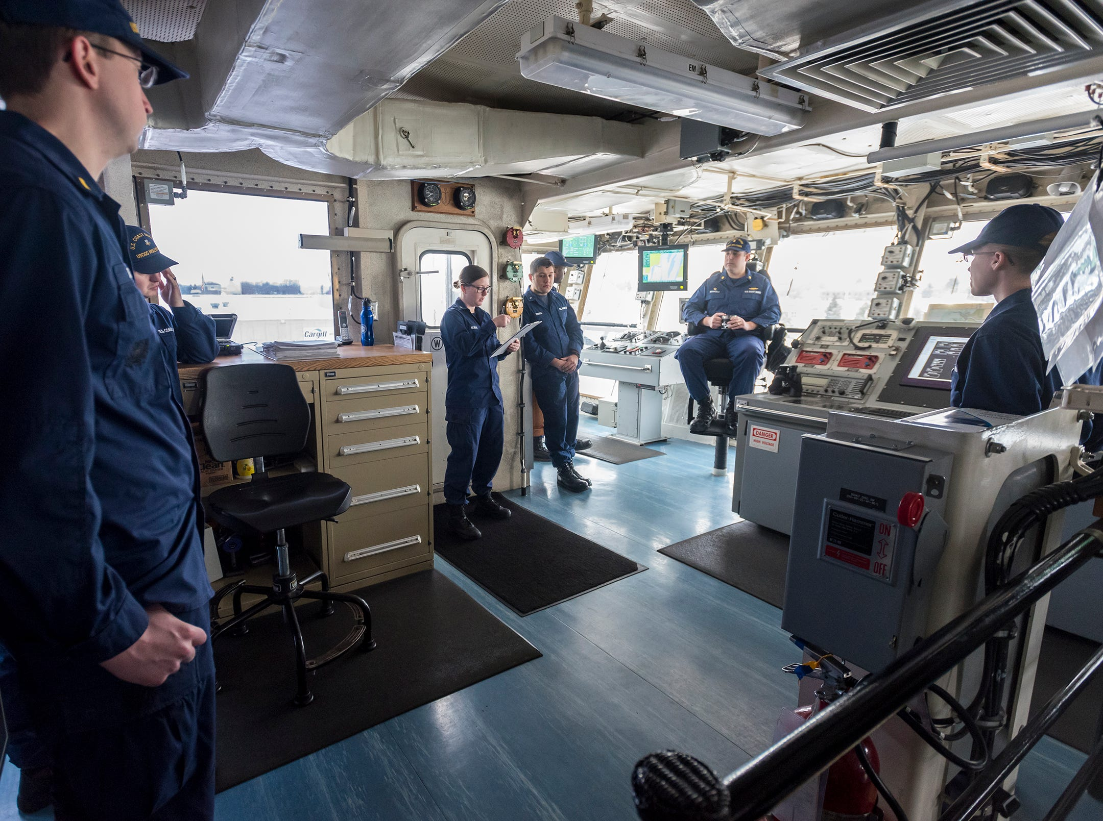 Some of the Hollyhock's crew meet for a short briefing on the ship's bridge before getting underway.