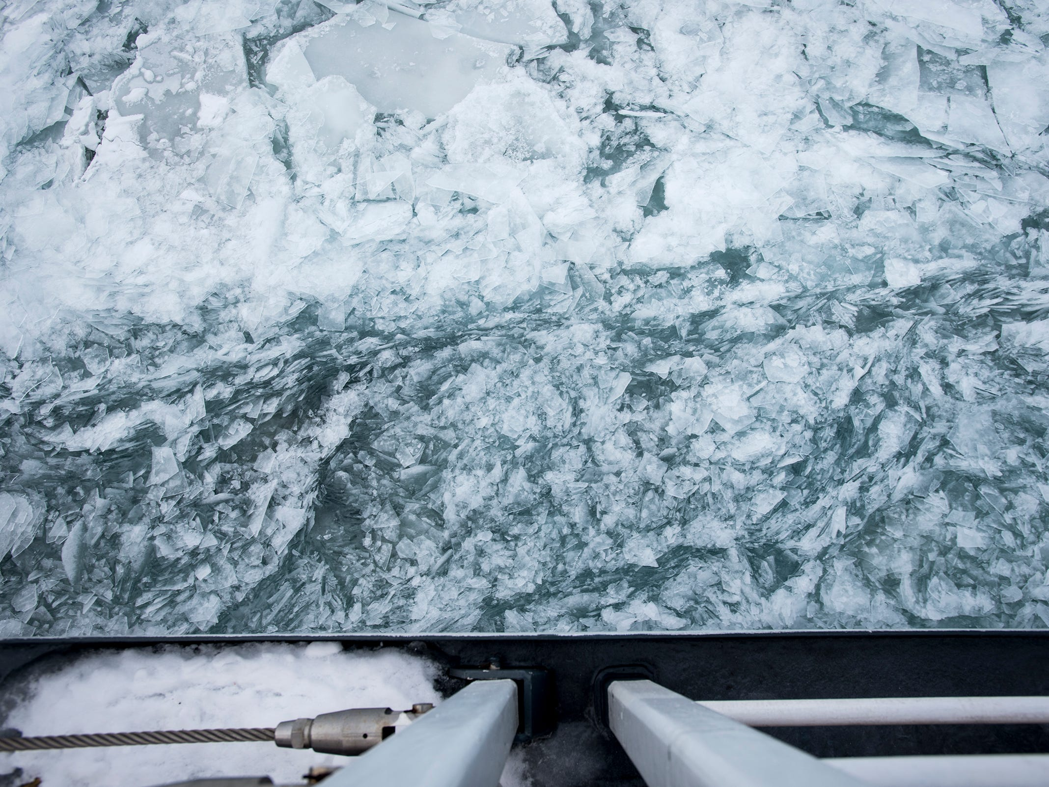 As the USCGC Hollyhock heads further south on the St. Clair River, more of the river's surface becomes hidden beneath ice. Chunks of ice that were broken apart by the freighter float past the ship as it presses onward.