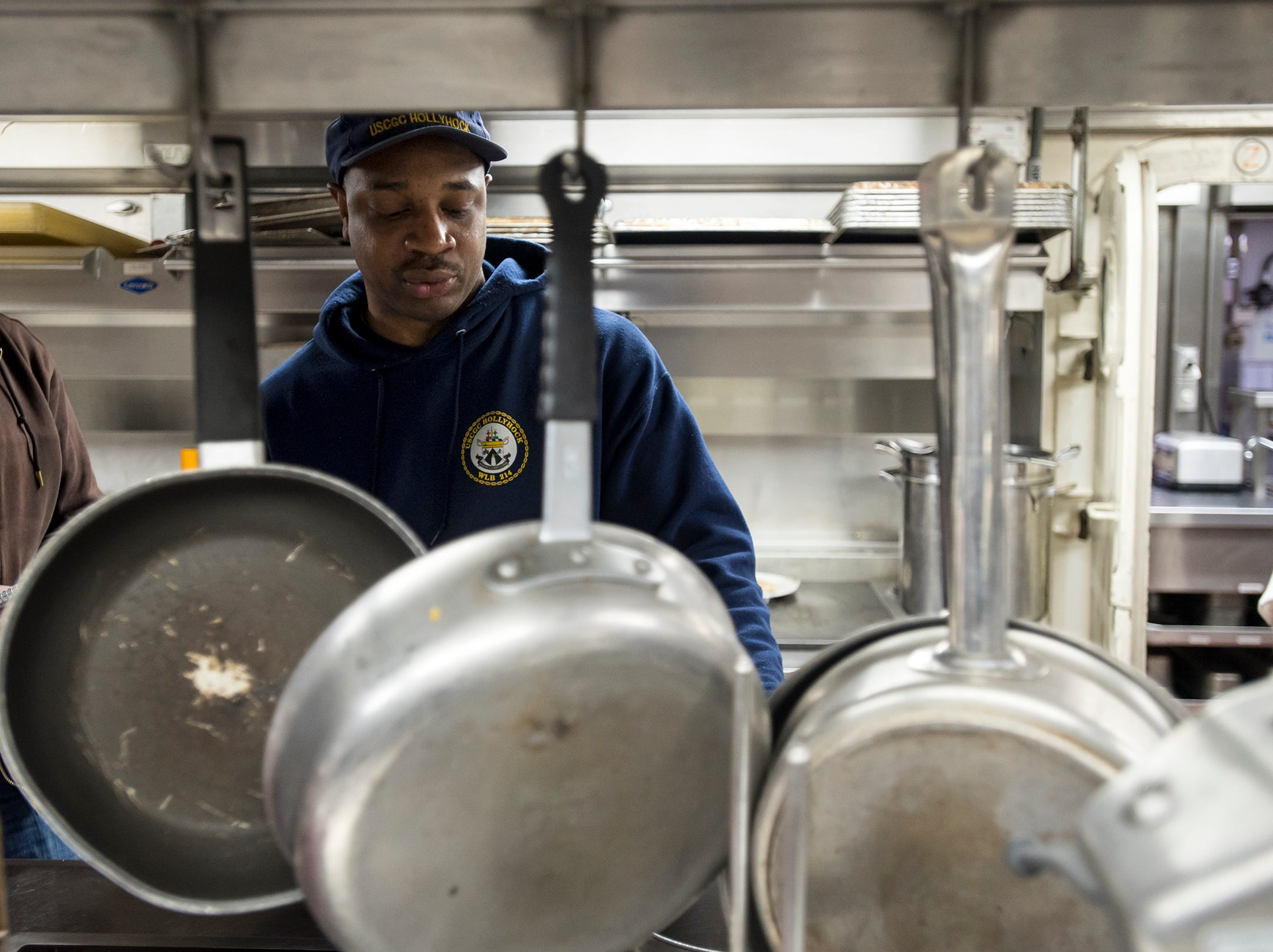 """CS2 Lee Johnson works in the kitchen aboard the USCGC Hollyhock after lunch Wednesday, Feb. 20, 2019. Johnson, of Alabama, said even though the kitchen works to make everything from scratch, the crew might give the cooks a hard time if a meal isn't satisfactory. """"We're the only job that gets judged three times a day,"""" Johnson said."""