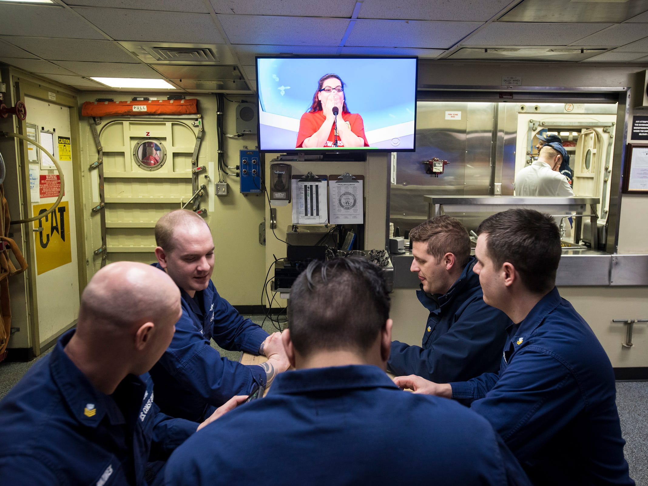 """Below deck, members of the Hollyhock's crew use their lunchtime to play a game of cards and watch """"The Price Is Right,"""" which is popular among crews throughout the U.S. Coast Guard. """"It's a good way for the crew to come together,"""" CS2 Lee Johnson, who works in the kitchen, said. """"...it's good morale."""""""