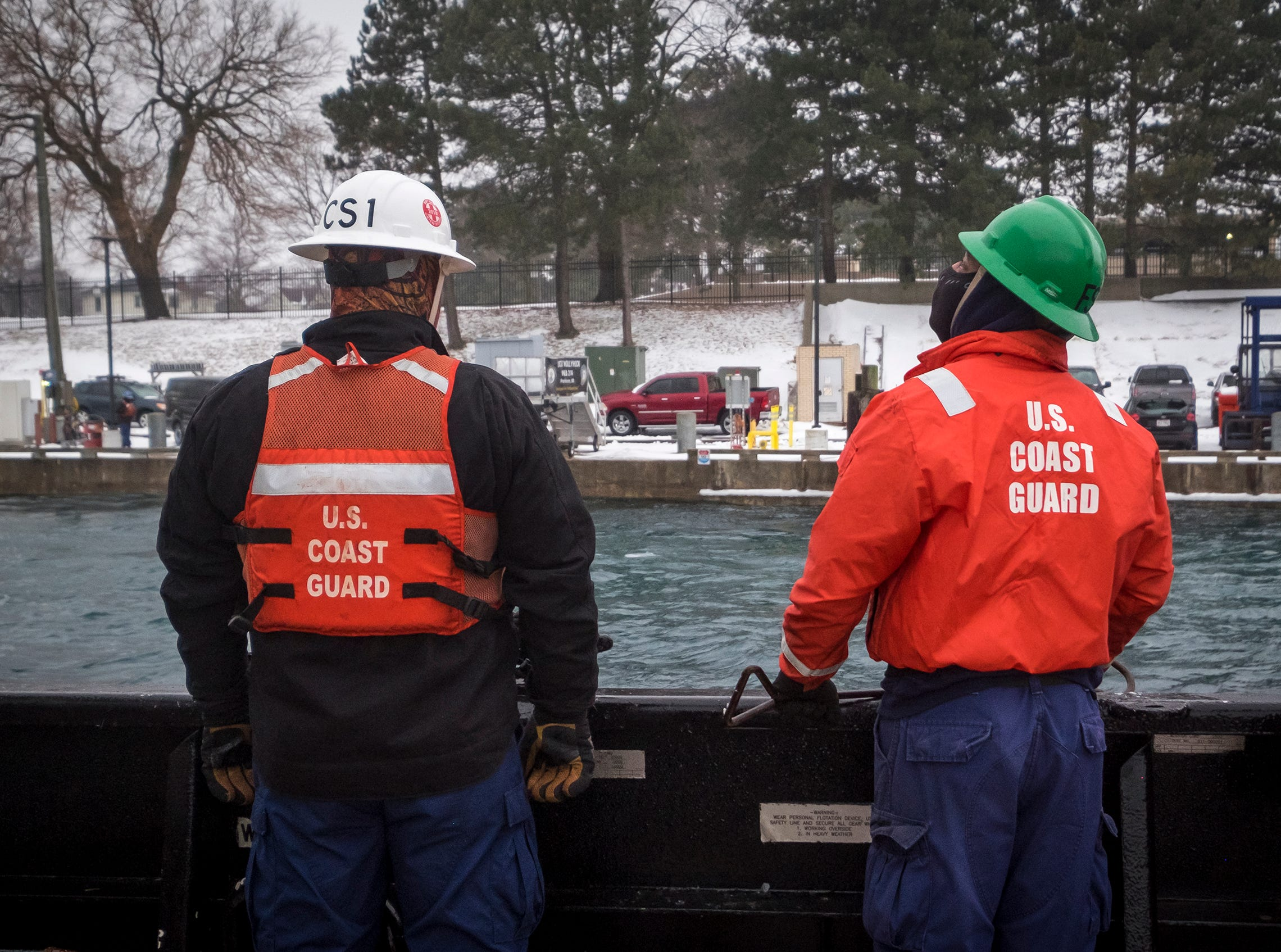 U.S. Coast Guard CS2 Lee Johnson, right, and CS1 Chip Dollahon wait on the deck of the Hollyhock as the ship nears its home port in Port Huron.