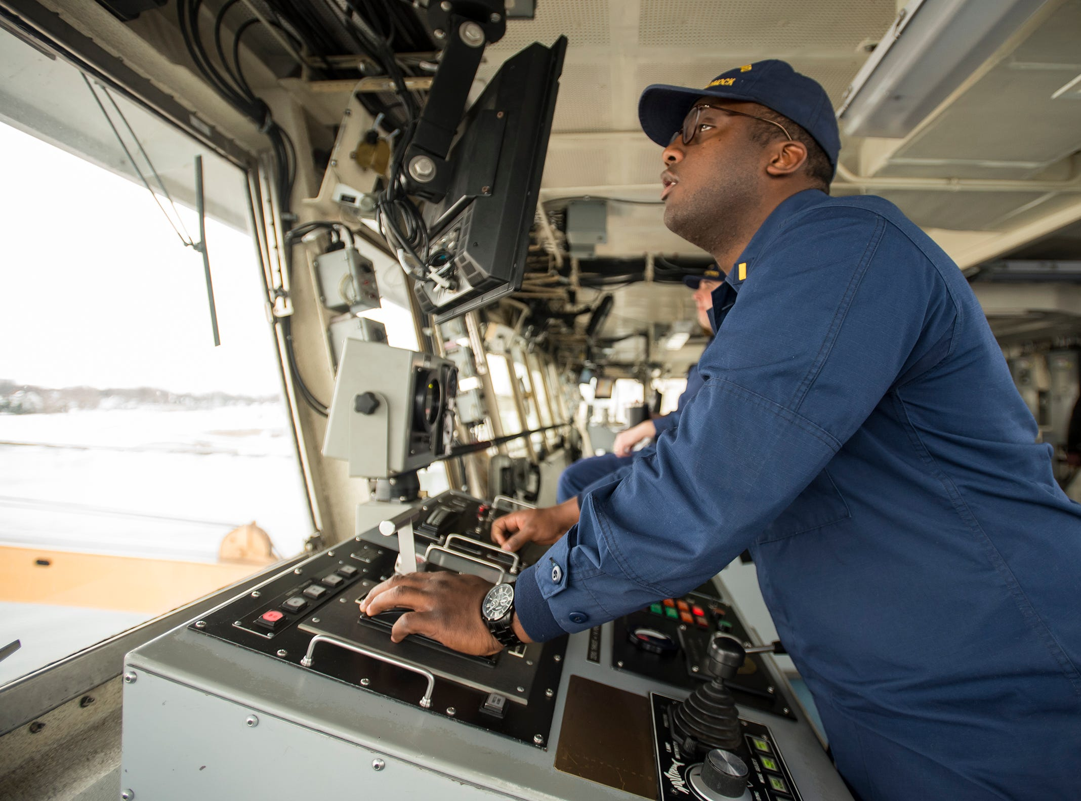 """Ensign Geremy Kendrick controls the Hollyhock using a control panel on the ship's bridge. Kendrick, of Florida, who enlisted right after graduating high school, says joining the Coast Guard was one of the best decisions he's ever made. """"You'll see things that nobody else has seen, and you'll do things that nobody else has done,"""" he said."""