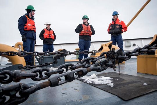 Ensigns Jesse Thrift and Kevin Wetmore, left and left of center, wait on the deck of the USCGC Hollyhock with Seaman Cameron Deweese, right of center, and BM3 Adam Haggerty Wednesday, Feb. 20, 2019 before releasing the ship's anchors. After successfuly escorting the Algonova, the ship anchored in the St. Clair River for maintenance.