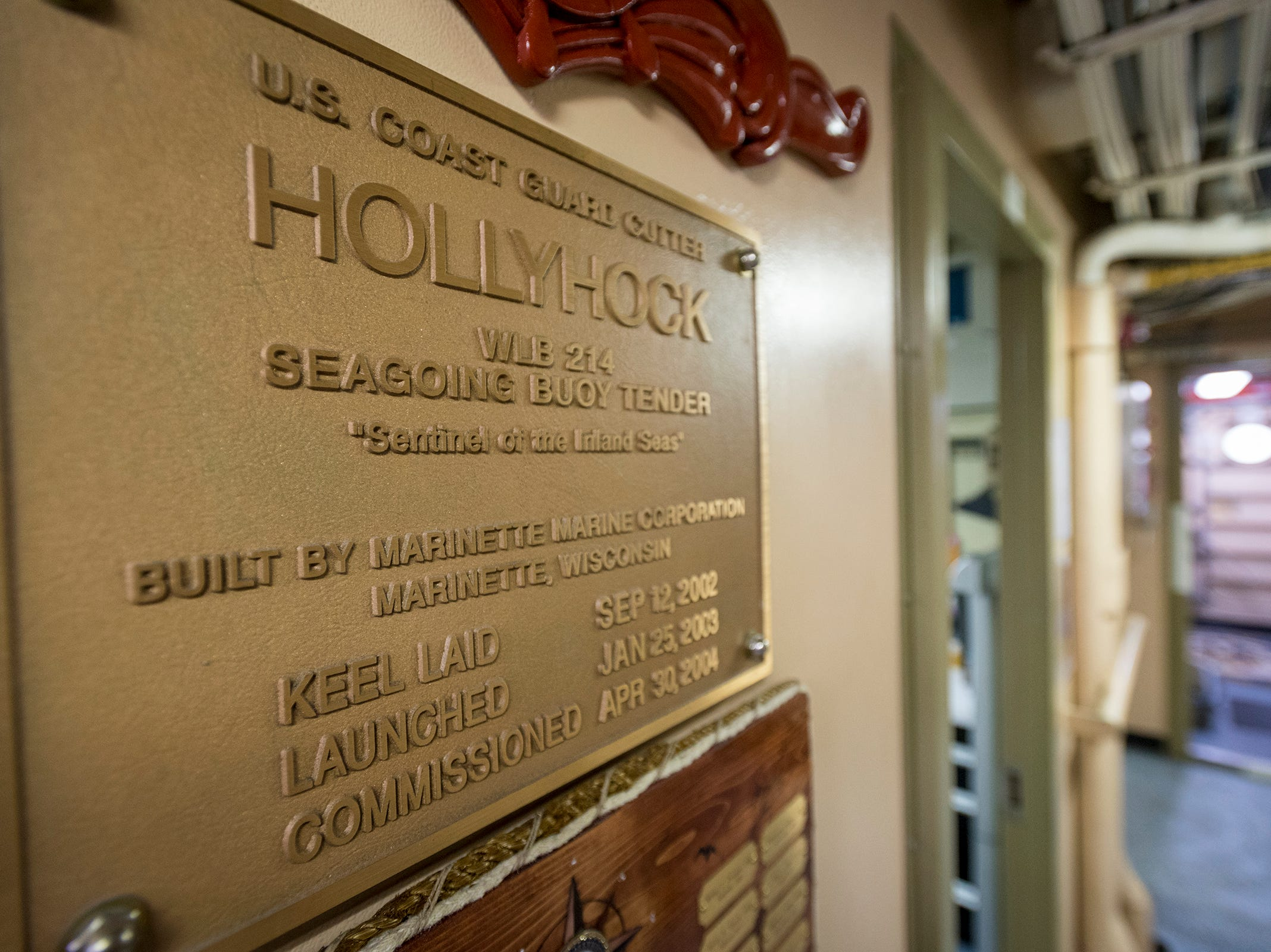 Photos and plaques showing the history of the Coast Guard and the USCGC Hollyhock can be seen throughout the ship's deck.