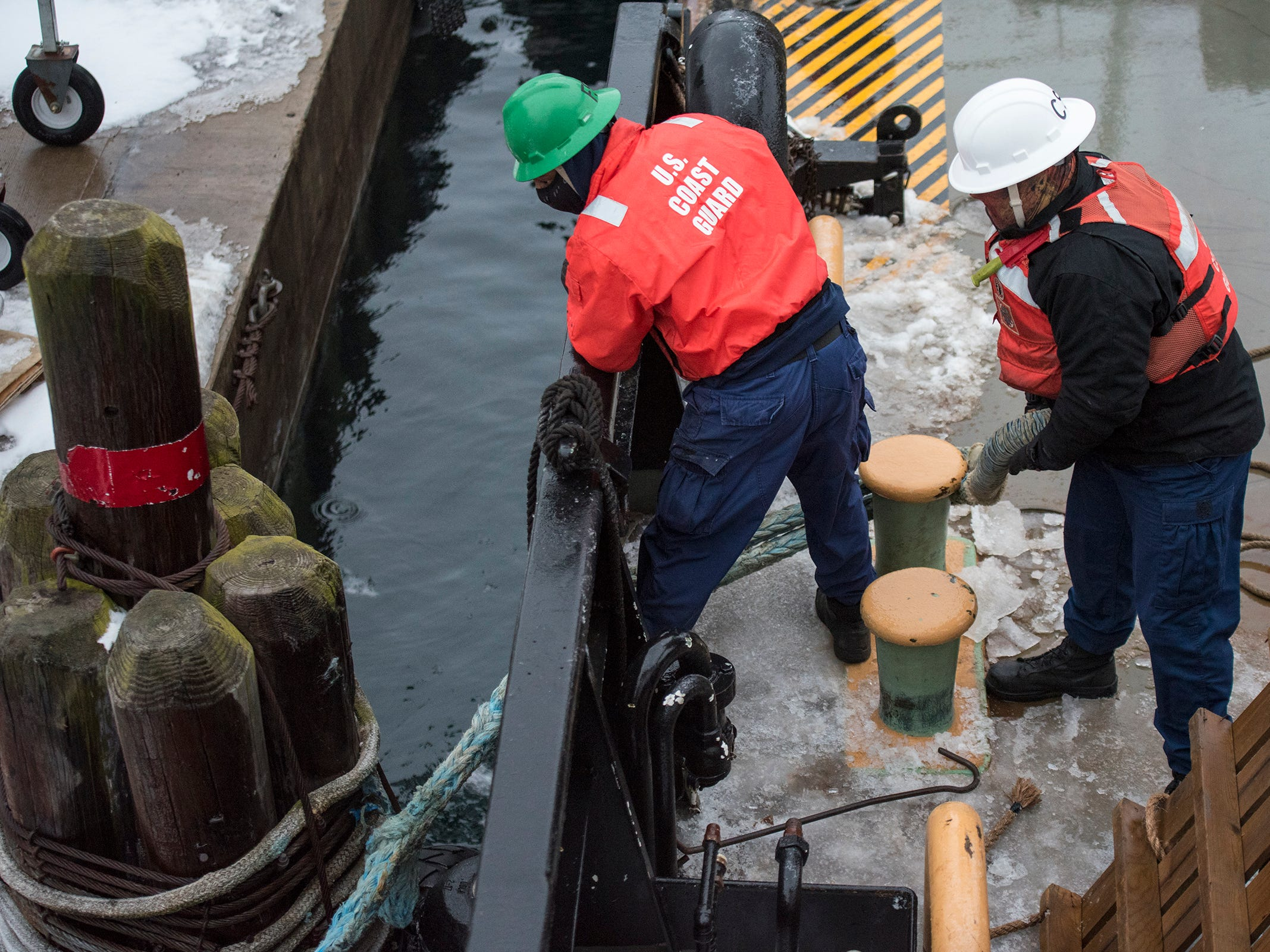 """U.S. Coast Guard CS2 Lee Johnson, left, and CS1 Chip Dollahon pull lines onto the deck of the USCGC Hollyhock as the crew works to dock it Wednesday, Feb. 20, 2019 in Port Huron. Johnson and Dollahon use the lines to pull the ship into position and secure it to the dock before pulling the bridge to the ship. """"Basically without us, nobody gets off the ship,"""" Lee said."""