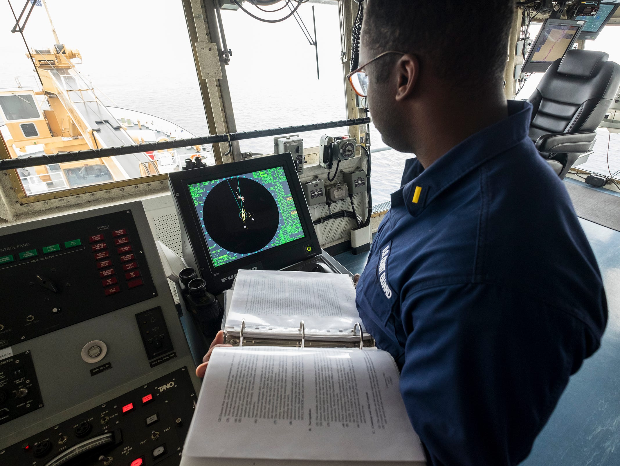 As rain and fog move into the area, Ensign Geremy Kendrick uses a radar on the Hollyhock's bridge to help detect land and other obstacles nearby.