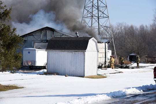 Firefighters work a barn fire in Cottrellville Township Thursday.