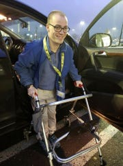 In this Dec. 14, 2018 photo provided by Holly Catlin, Adam Catlin gets out of a car before starting his shift at a Walmart in Selinsgrove, Pa. Catlin, who has cerebral palsy, is afraid he'll be out of work after store officials changed his job description to add tasks that he's physically unable to do. (Holly Catlin via AP)