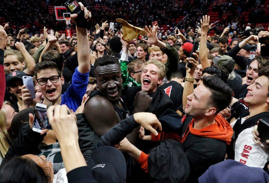 San Diego State forward Aguek Arop, center left, is swarmed by fans after the Aztecs beat Nevada, 65-57, on Wednesday.