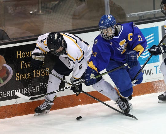Irondequoit's Jack Feola (17) and Thomas' Nate Kernan  fight for the puck along the end board.