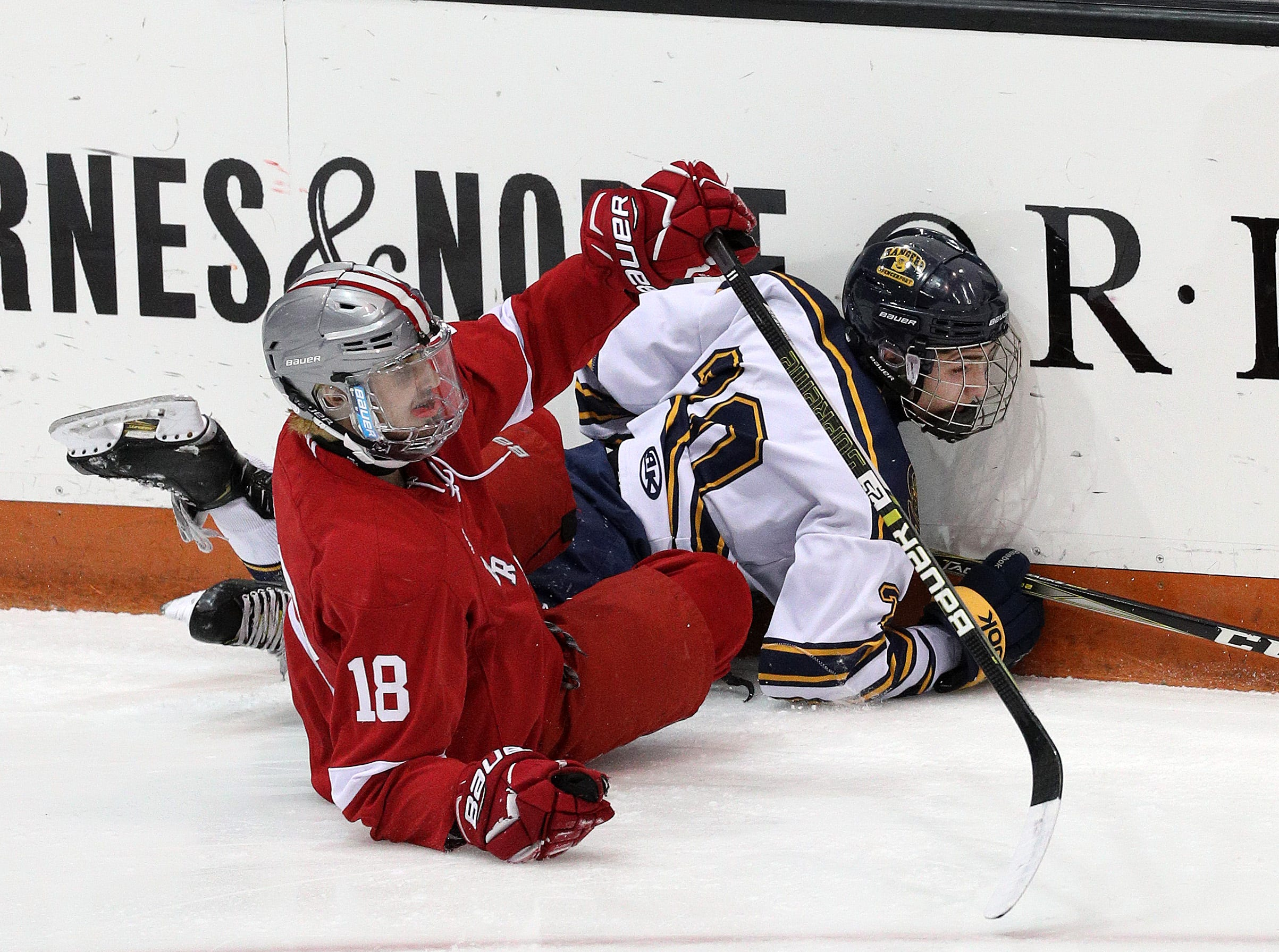Spencerport's AJ Giannavola is checked into the boards by Canandaigua's Michael Cichetti.