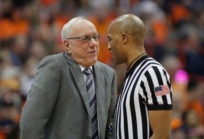 Syracuse head coach Jim Boeheim, left, talks to an official about a call during the second half of an NCAA college basketball game against Louisville in Syracuse, N.Y., Wednesday, Feb. 20, 2019. Syracuse won 69-49.