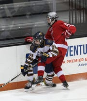 Spencerport's AJ Giannavola is tied up behind the net by Canandaigua's Matt McMullen.