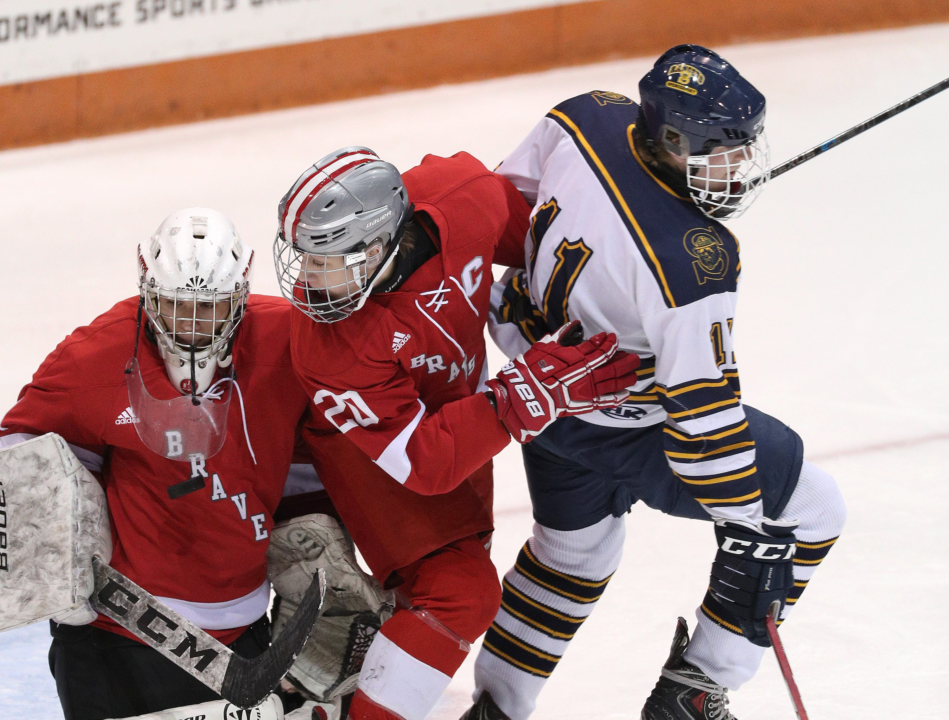 Canandaigua goalie Cade Chesler stops this shot as teammate Ryan Pitka tries to clear away Spencerport's Parker Scholand (11).