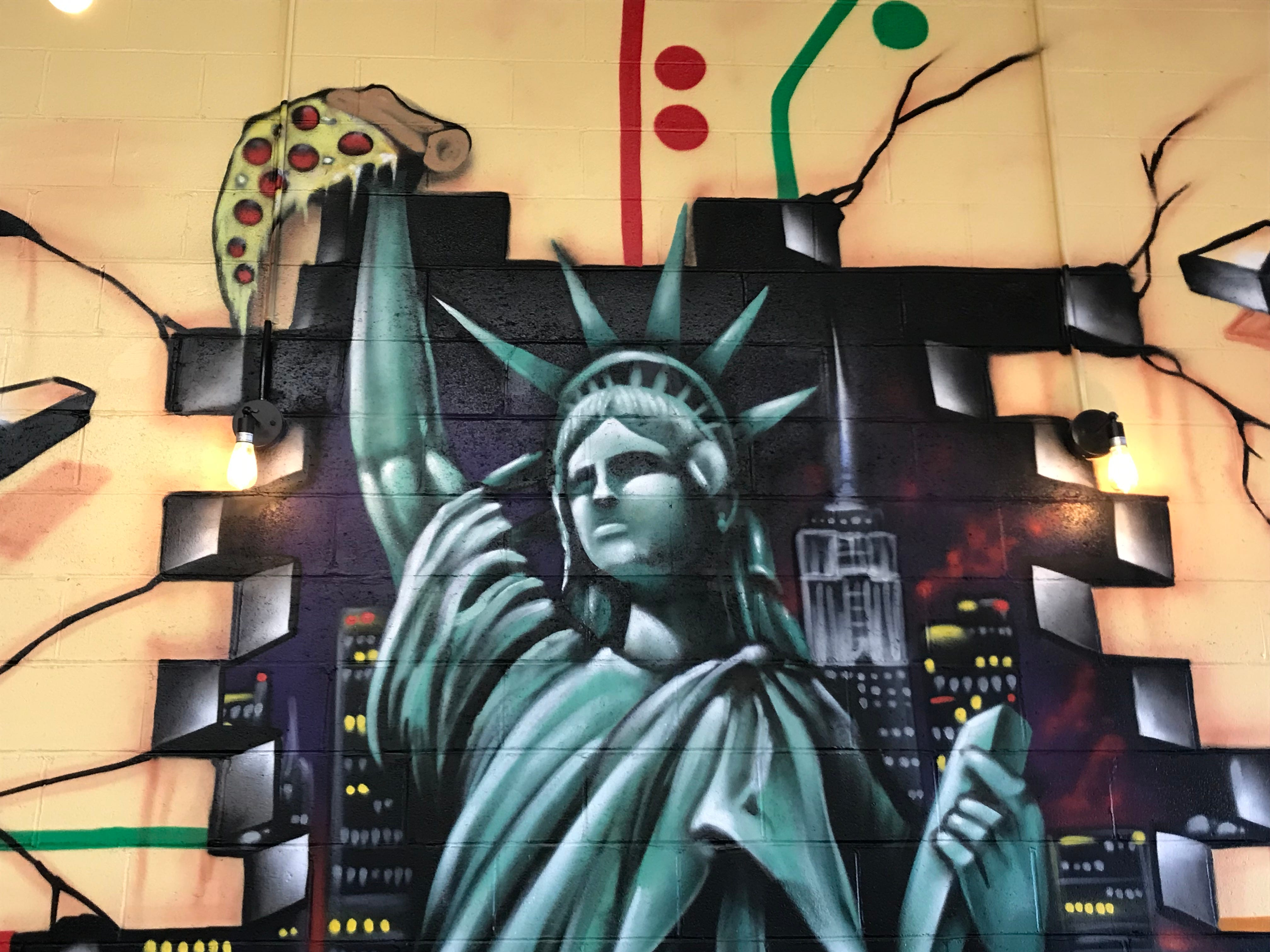 The Statue of Liberty holding a slice of pizza is the focal point of a mural at the Pittsford Stop in Pittsford Plaza.