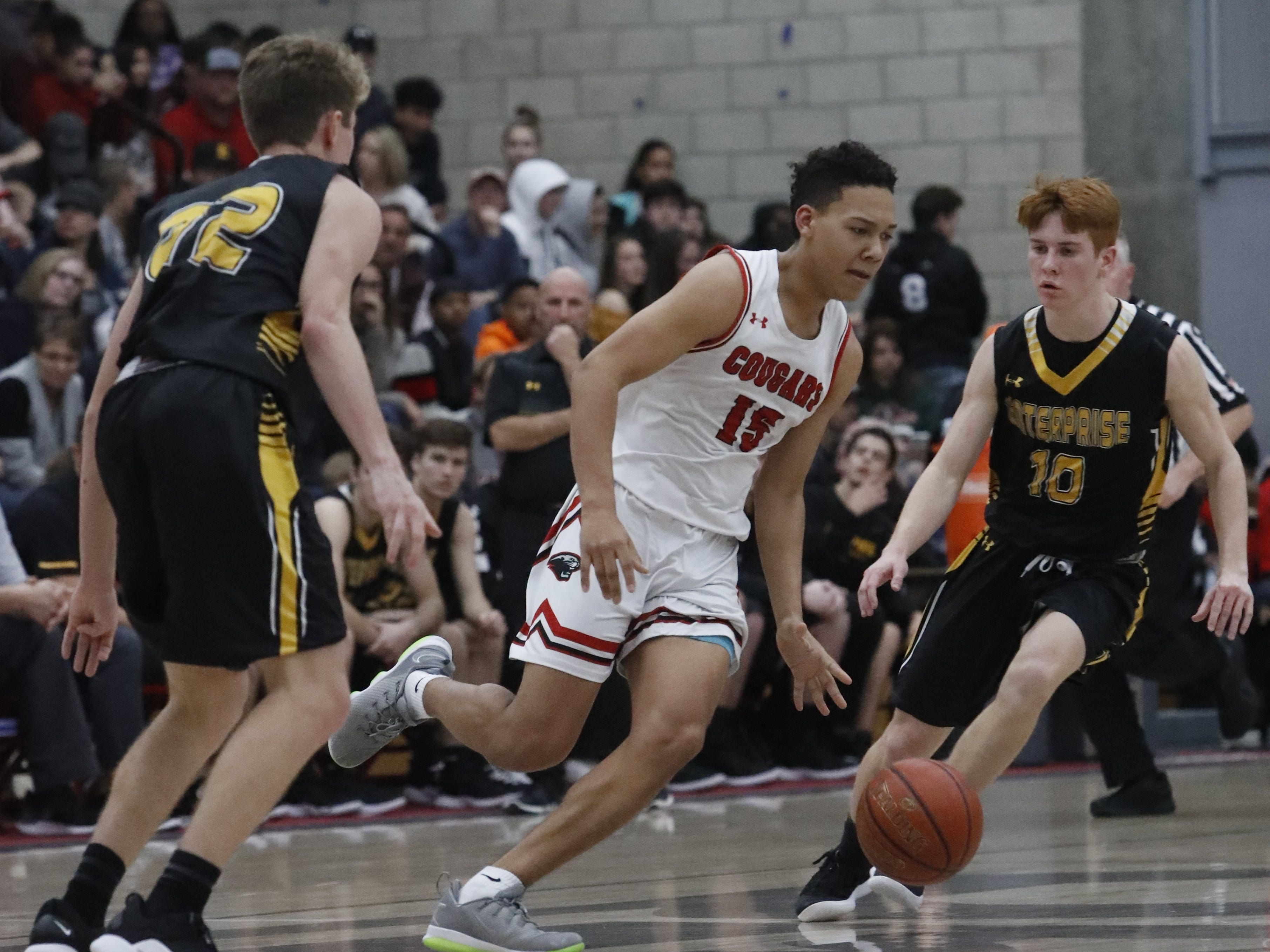 Foothill senior Josiah Hutt (center) dribbles between two Enterprise defenders during the Cougars' 55-50 win over the Hornets  in the Division III Northern Section semifinals on Wednesday, Feb. 20.
