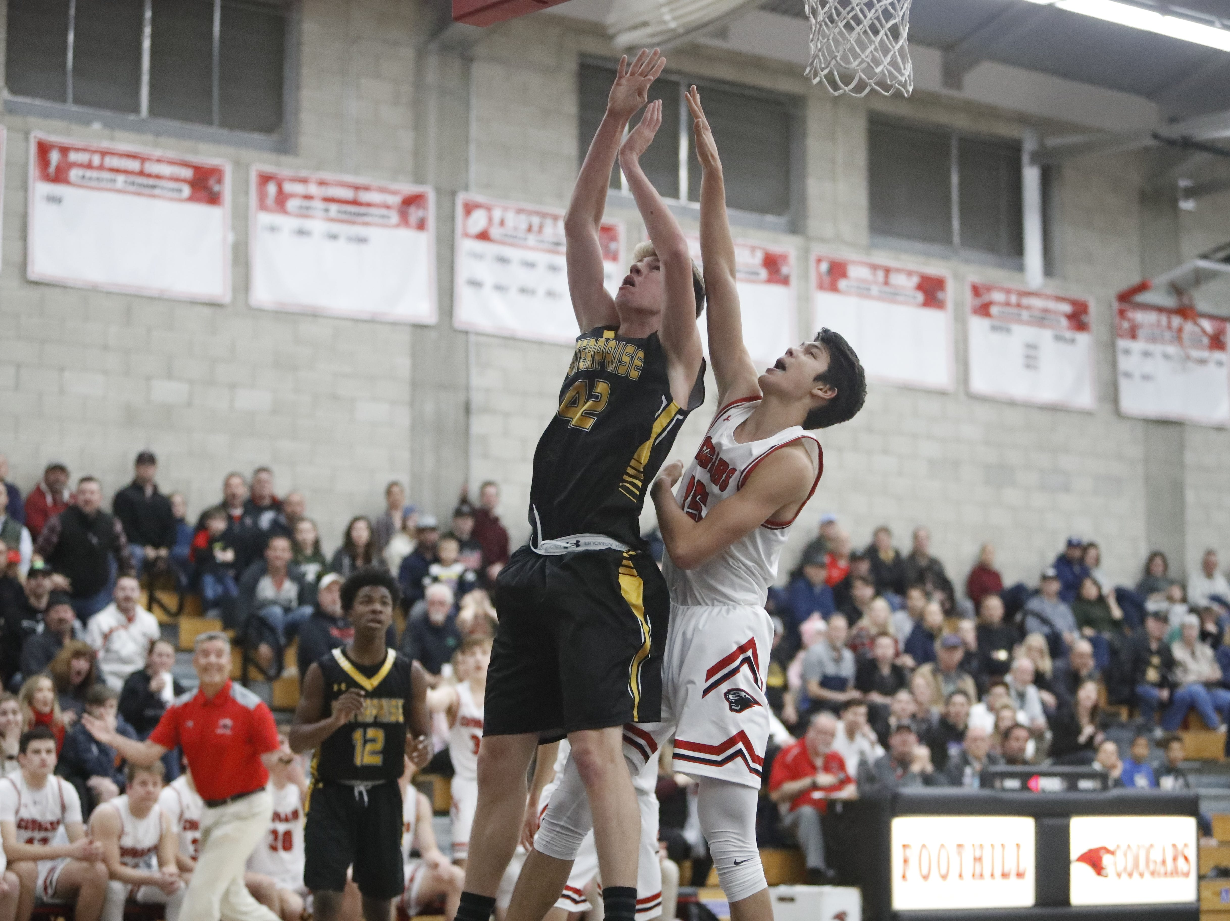 Enterprise senior Khristian Clements (left) fights for a rebound with Foothill's Bekdoo Lewis during the Cougars' 55-50 win over the Hornets  in the Division III Northern Section semifinals on Wednesday, Feb. 20.