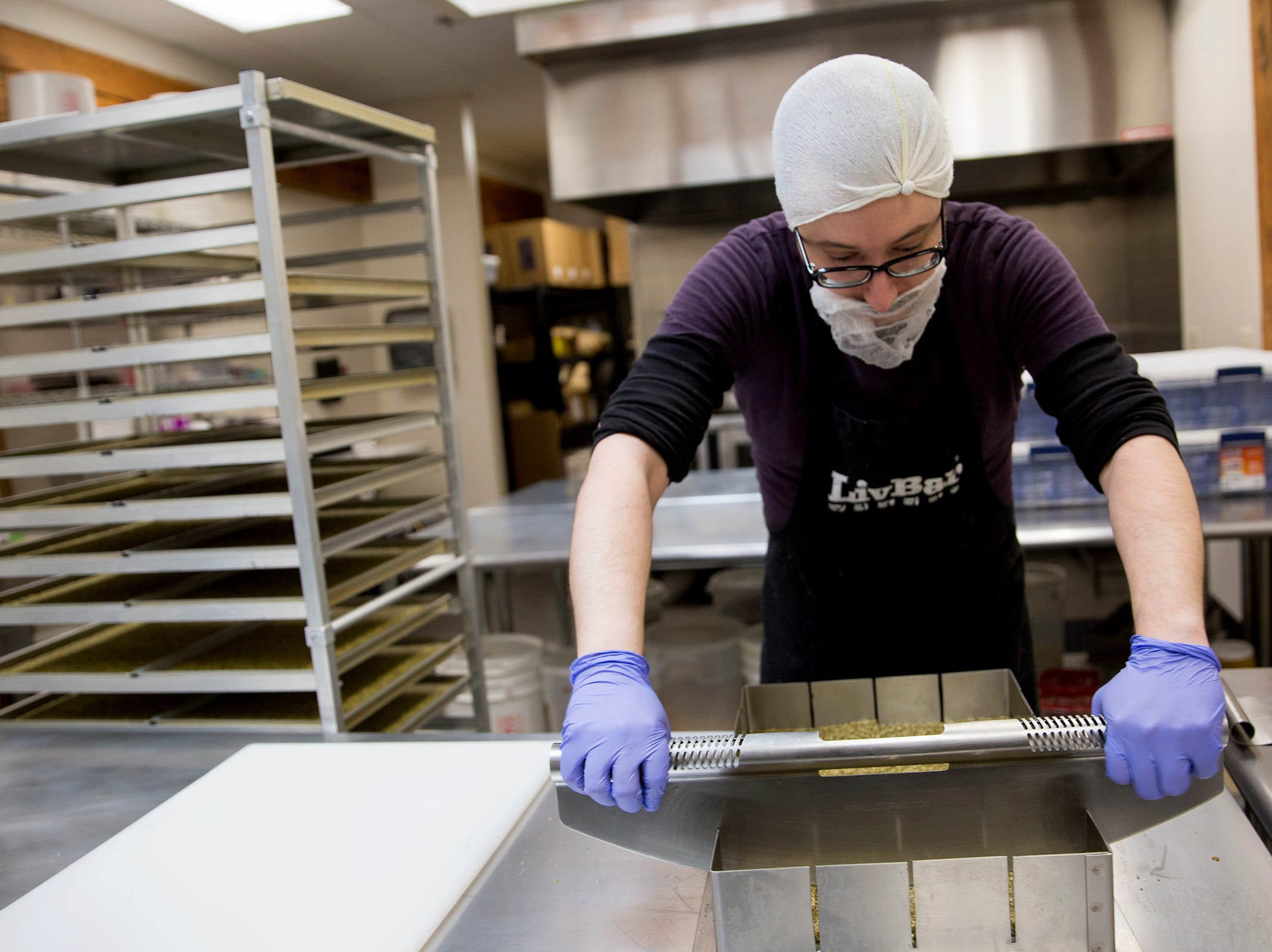 Kitchen manager Aldo Arevalo cuts into a sheet of raspberry kale maca-flavored LivBar energy bars in their kitchen in downtown Salem on Wednesday, Feb. 20, 2019.