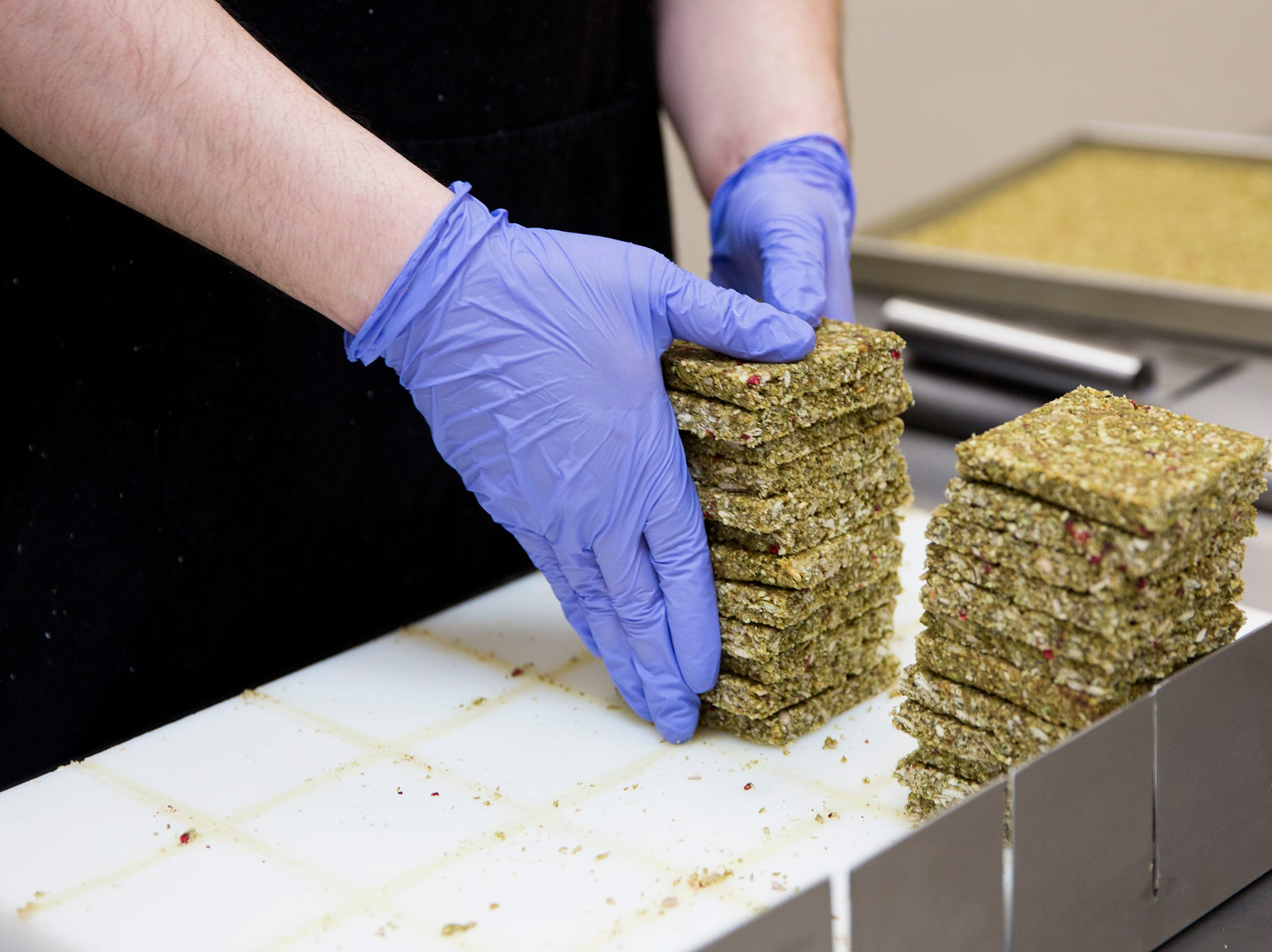 Kitchen manager Aldo Arevalo stacks squares of kale maca-flavored LivBar energy bars in their kitchen in downtown Salem on Wednesday, Feb. 20, 2019.