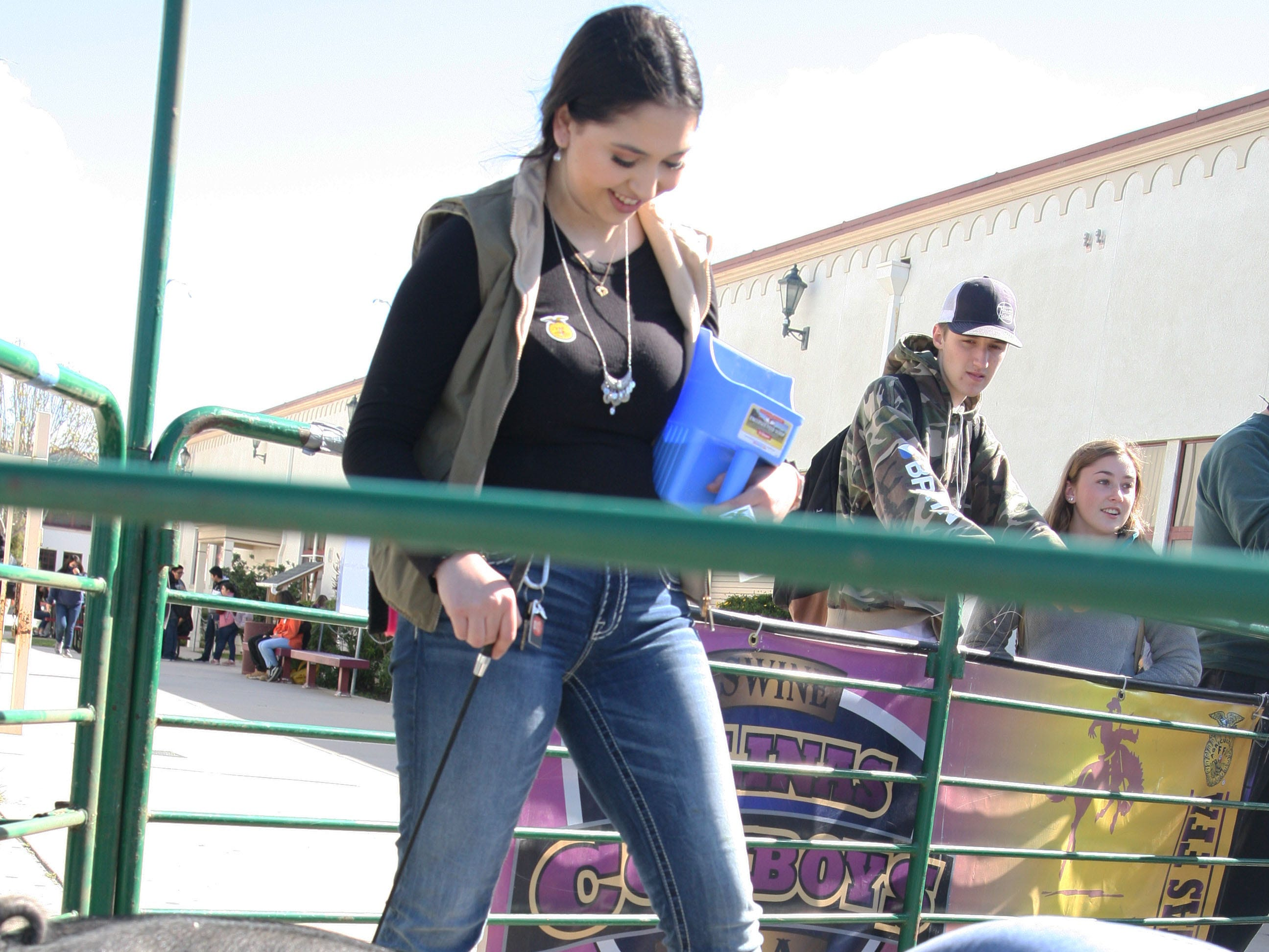 Angela Macias watches another student interact with her pig, Zola.
