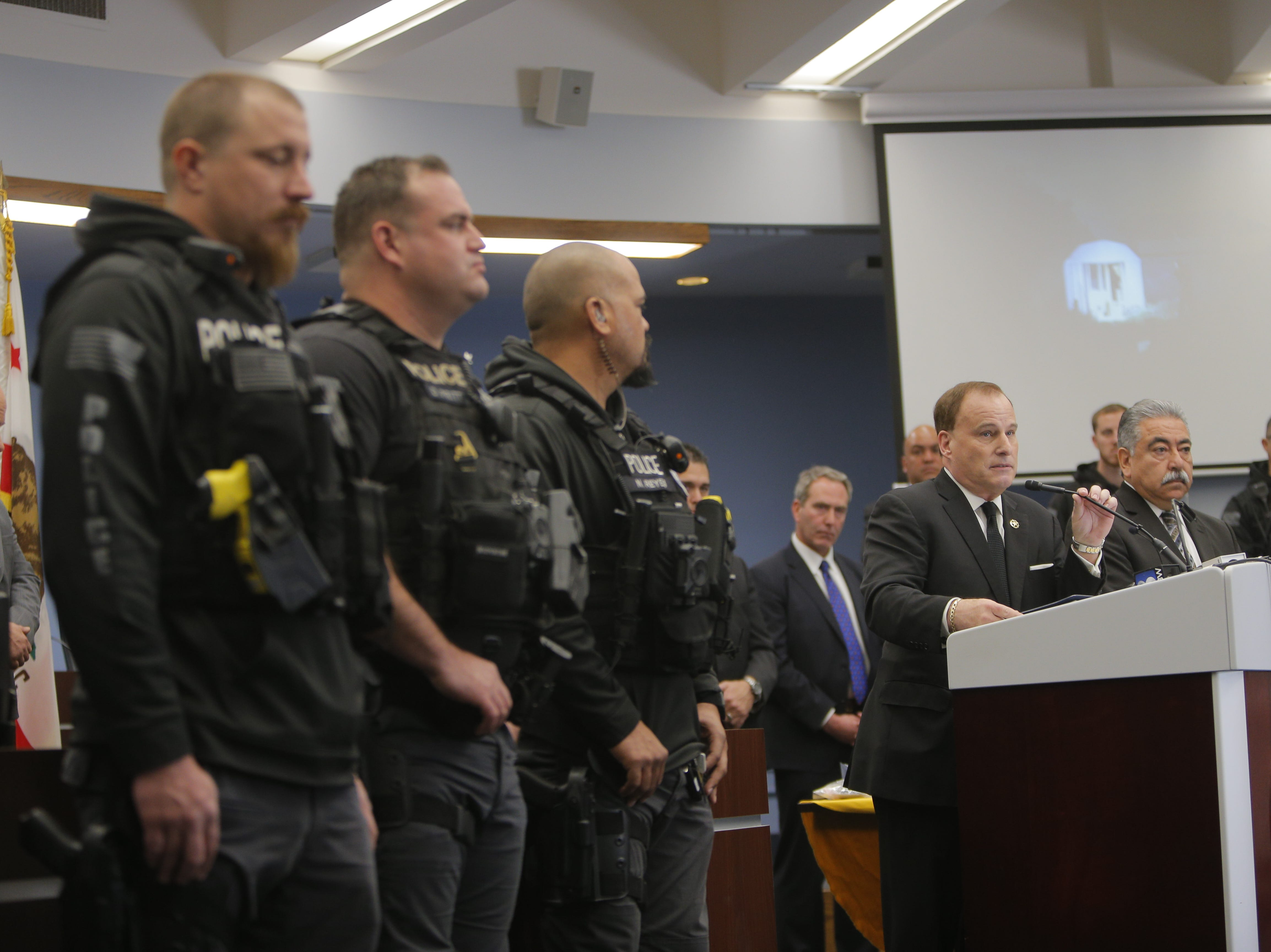 Salinas police officers listen as U.S. Marshal Donald O'Keefe addresses Thursday's press conference for the Salinas Police Department's Triple Beam Operation, a collaborative counter gang initiative conducted in partnership with local, state and federal law enforcement.