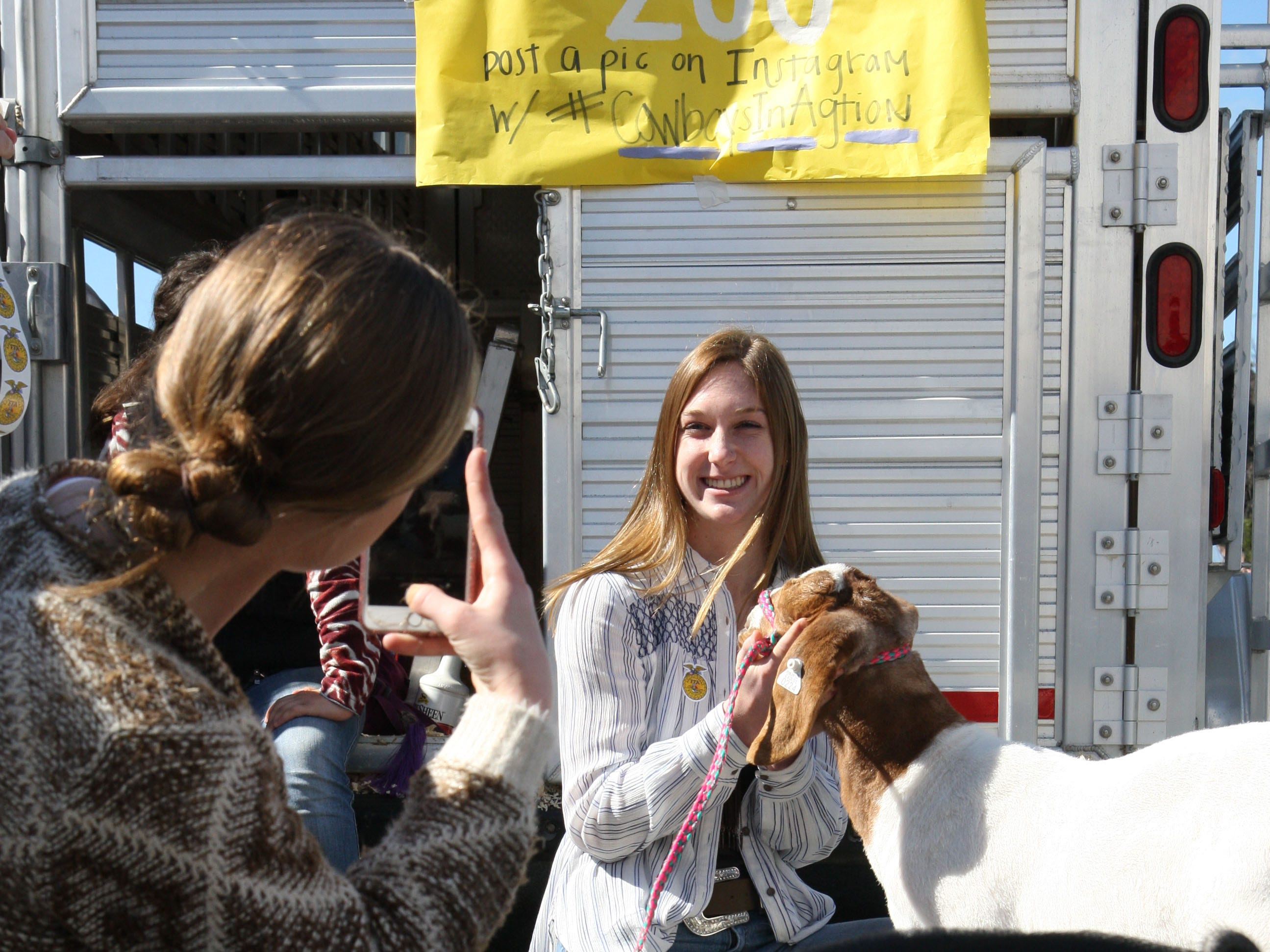 One of the students takes a photo of another student posing with a goat.