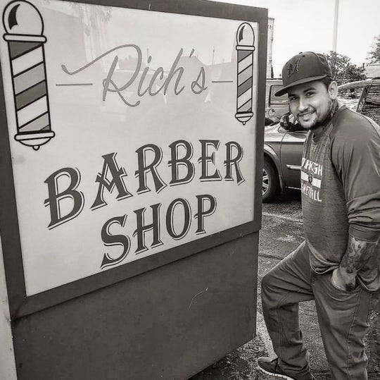 """Barber Rich"" poses in front of his shop."