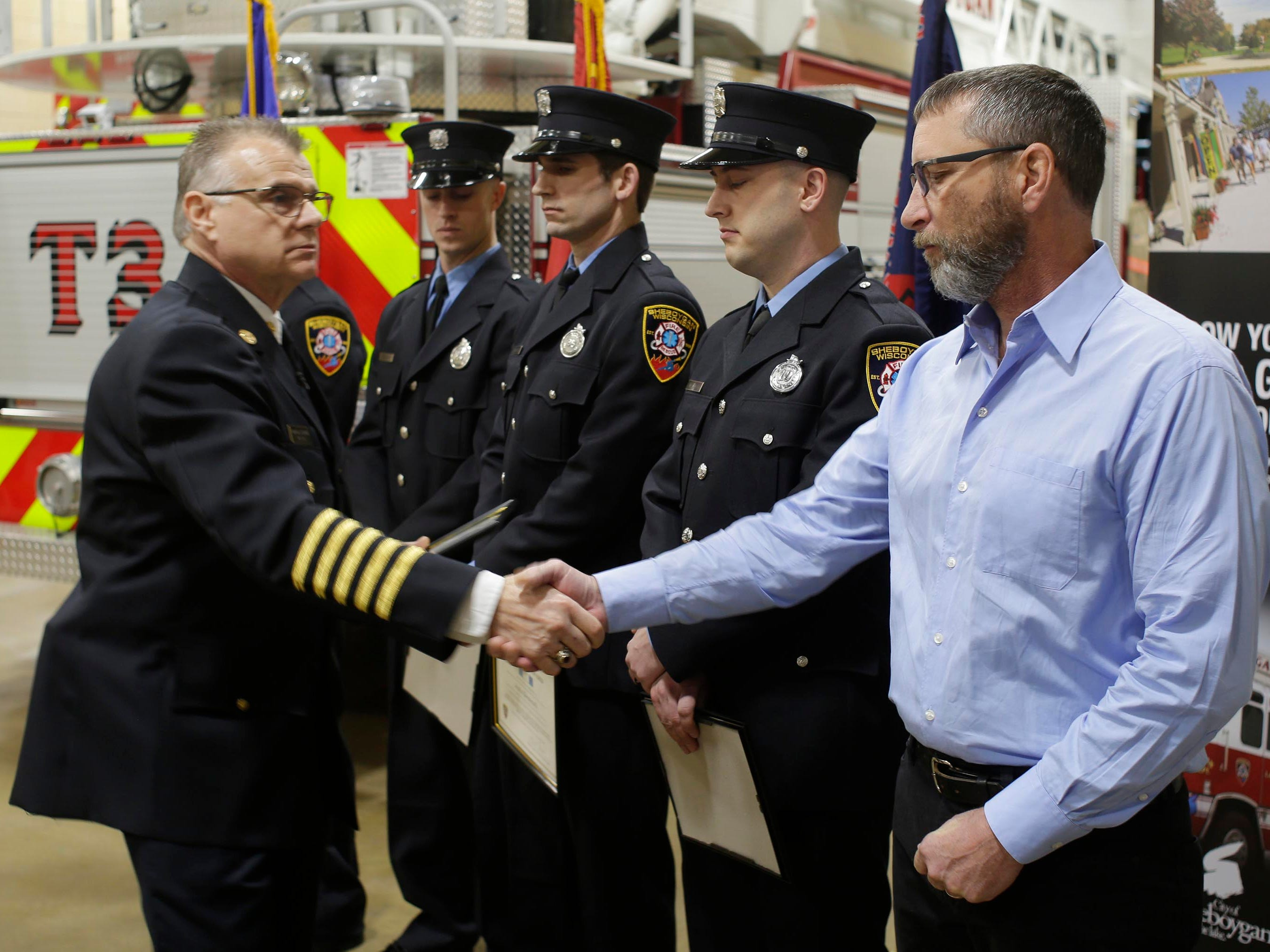 Sheboygan Fire Chief Mike Romas shakes the hand of retired firefighter Kurt Spatt, Wednesday, February 21, 2019, in Sheboygan, Wis.