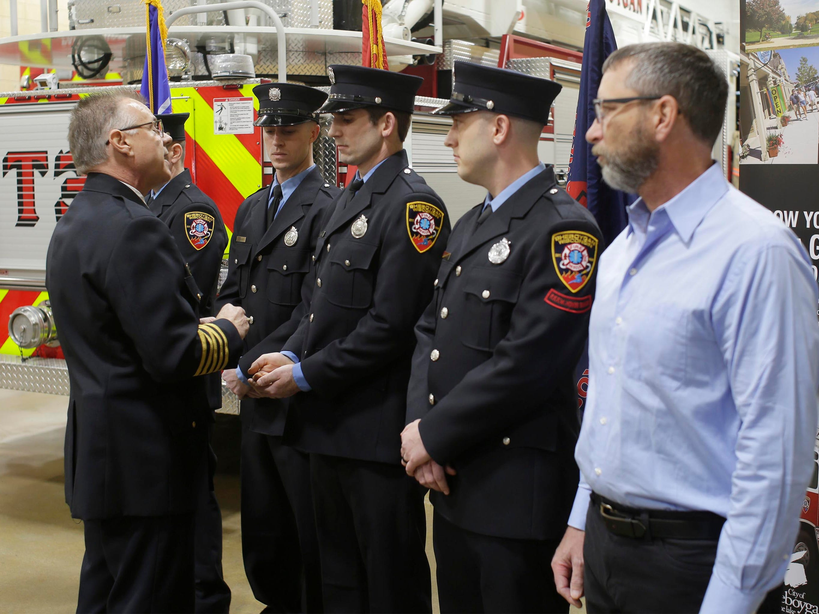 Sheboygan Fire Chief Mike Romas hands out awards to firefighters who saved the life of a youngster, Wednesday, February 21, 2019, in Sheboygan, Wis.
