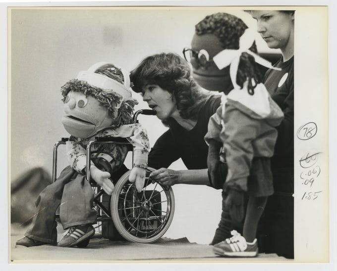 Puppeteer Susan Appleby operating a puppet in a wheelchair which was used in a puppet show for handicapped children at the United Cerebral Palsy Center in September of 1983.